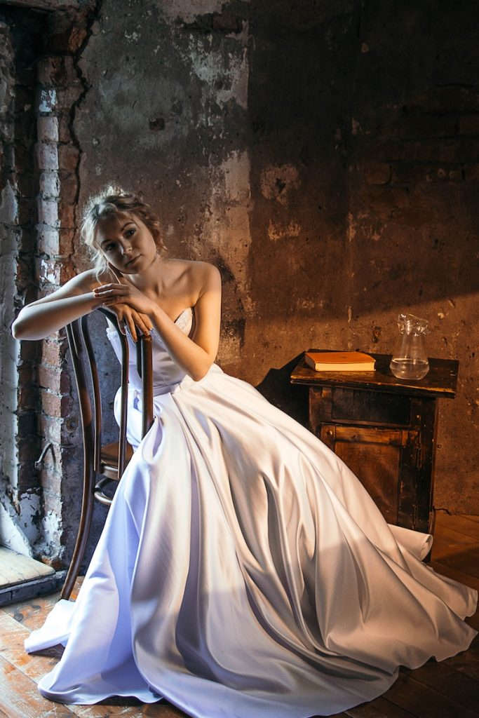 Cinderella in a white gown, sitting in a shabby room, gazing as if daydreaming